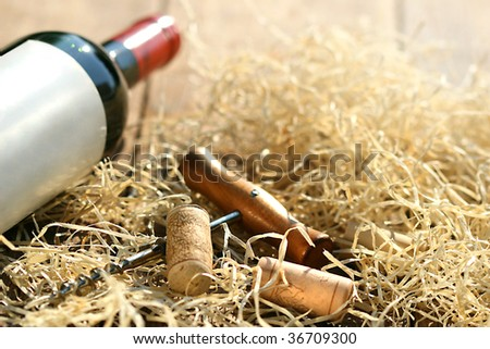 Bottle of red wine with corkscrew and packing straw