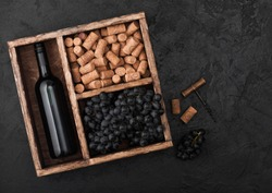 Bottle of red wine with dark grapes with corks and opener inside vintage wooden box on black background.