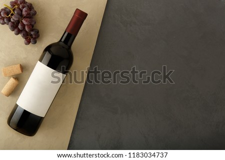Bottle of red wine with label. Glass of wine and cork. Wine bottle mockup. Top view.