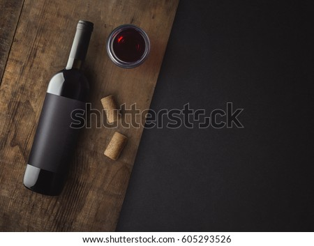 Bottle of red wine with label on old board. Glass of wine and cork. Wine bottle mockup. Top view.