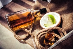 Bottle of rum with lime ice and coconut, coconut glasses and rum