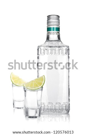 Bottle of silver tequila and two shots with lime slice. Isolated on white background