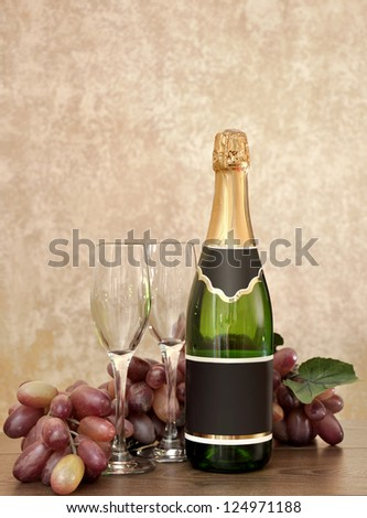 Bottle of sparkling wine, two glasses and grapes