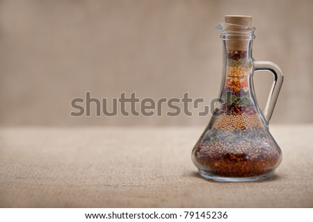 Bottle of spices. Capacity with a set of various spices on a rough background.