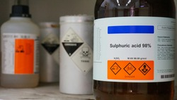 Bottle of Sulfuric Acid, H2SO4 with Properties information and its chemical hazard warning symbols. Corrosive hazard symbol, Inhalation hazard symbol and Toxic symbol