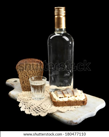 Bottle of vodka, sandwich with salted fish and glasses on wooden board, isolated on black