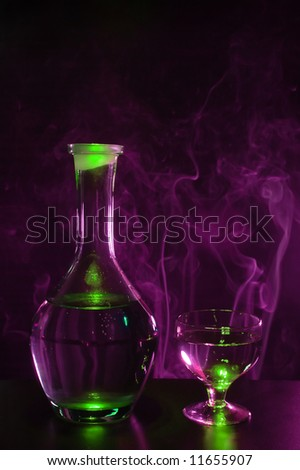 Bottle of vodka with glass and violet smoke