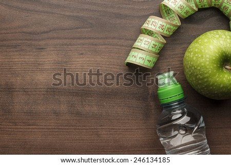 Shutterstock bottle of water, measuring tape and fresh green apple on the wooden table