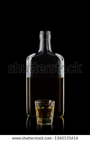 Bottle of whiskey and a glass of whiskey isolated on a black background with reflections. 100 sharpness. 100 sharpness.