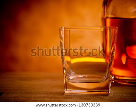 Bottle of whiskey with an empty glass waiting to be filled