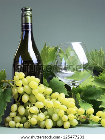 Bottle of white wine, wine glass with a large bunch of grapes and grape vine leaves. Vertical portrait orientation.