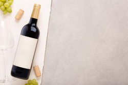 Bottle of white wine with label. Glass of wine and cork. Wine bottle mockup. Top view.