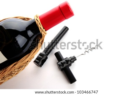 bottle of wine and a corkscrew on white background with copyspace