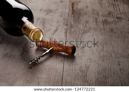 bottle of wine and corkscrew over wooden background
