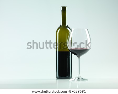 bottle of wine and glass with red wine, copy space