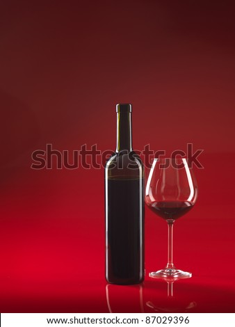 bottle of wine and glass with red wine, on red background, copy space