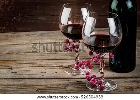 Bottle of wine and two glasses of wine, decorated with artificial branch of winter berries. The festive mood, Valentine\'s Day, Thanksgiving or Christmas. Copy space.