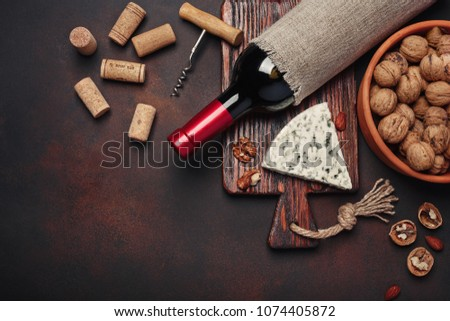 Bottle of wine, blue cheese, walnut, almonds, corkscrew, rope and corks, on rusty background top view