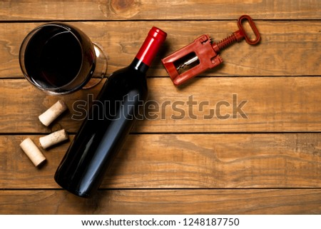 Bottle of wine glass corkscrew and corkscrew on wooden background. Top view with copy space. #1248187750