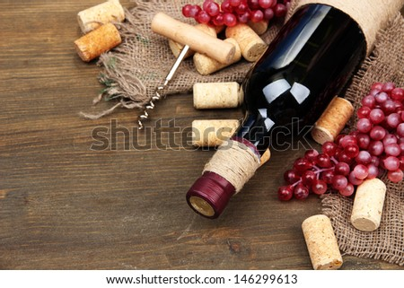 Bottle of wine, grapes and corks on wooden background #146299613