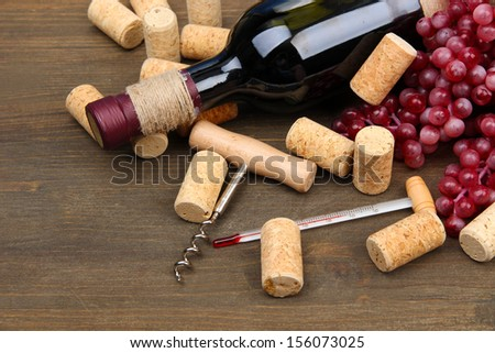 Bottle of wine, grapes and corks on wooden background #156073025