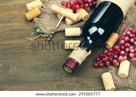 Bottle of wine, grapes and corks on wooden background #291005777