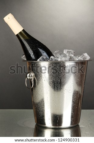 Bottle of wine in ice bucket on black background