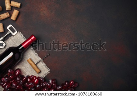 Bottle of wine, red grapes, corkscrew and corks, on rusty background top view, copy space