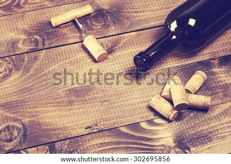Bottle of wine with corkscrew on wooden background #302695856