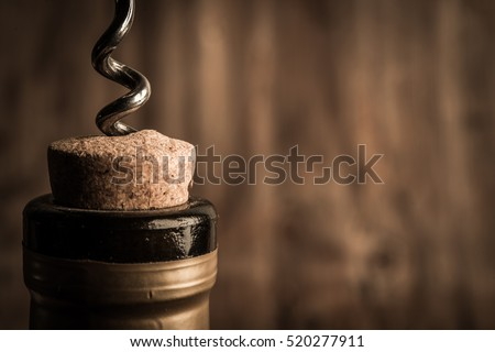 Shutterstock Bottle of wine with corkscrew on wooden background
