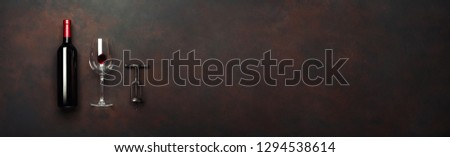 Bottle of wine with wineglass and corkscrew on rusty brown background. Panoramic top view with copy space for your text. #1294538614