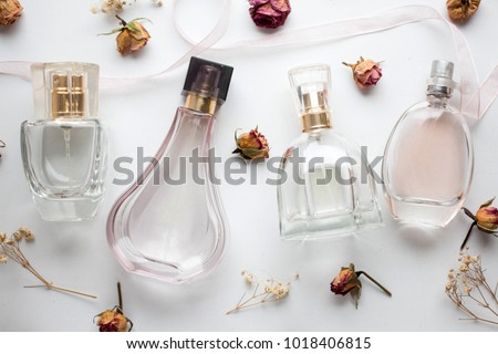 bottle of woman perfume on white background with roses. gift. #1018406815