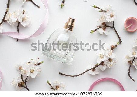 bottle of woman perfume on white background with spring apricot and cherry flowefs. gift. pink ribbon #1072876736