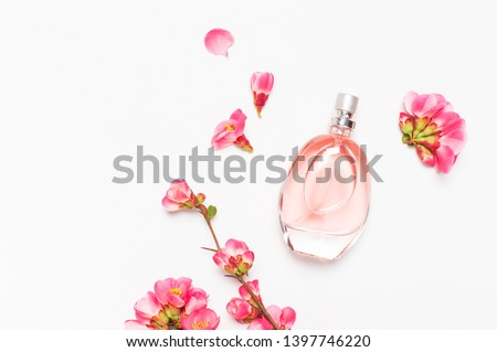 Bottle of women's perfume with pink spring flowers on light gray background top view flat lay copy space. Perfumery, cosmetics, female accessories, fragrance collection. Delicate Pink Perfume Bottle #1397746220