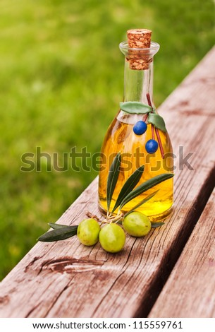 Bottle  olive oil with fresh green olives