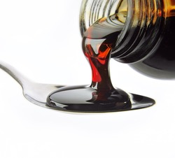 bottle pouring cough syrup into a spoon