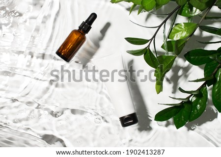 Bottle serum, oil cosmetic in clean transparent water with green leaf, sunlight on white background, flat lay, top view, copy space Foto d'archivio ©