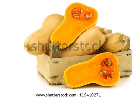 bottle shaped butternut pumpkins and two halves in a wooden crate on a white background - stock photo