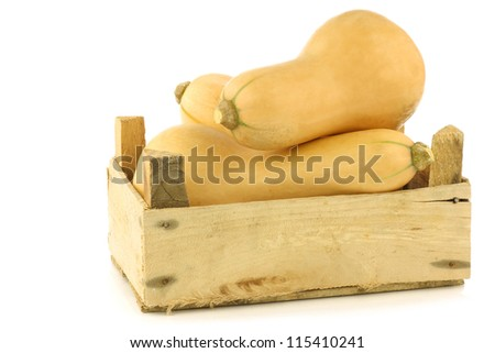 bottle shaped butternut pumpkins in a wooden crate on a white background