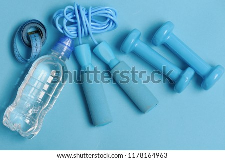 Bottle, tape roll, cyan dumbbells and skipping rope on blue background. Health regime and fitness symbols. Jump rope, water bottle, measure tape and barbells, topview. Fit shape and sport concept