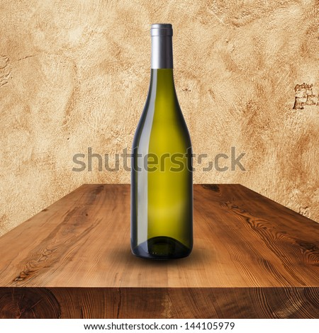 Bottle white wine on wood table and grunge wall