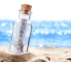 Bottle with a message for help. Sea beach.
