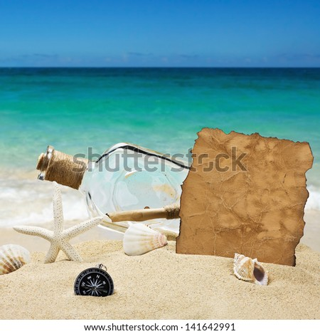 bottle with a note on the background of the sea beach