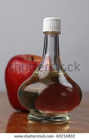 Bottle with apple vinegar and fresh apple. Shallow dof