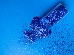 Bottle with blue color glitter inside on blue trendy background. Trendy blue color concept. Copy Space