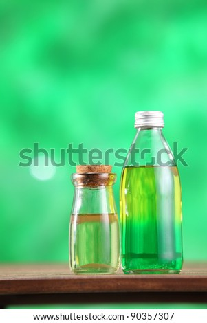 Bottle with massage oil on the green background