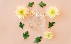 bottle with perfume, yellow flowers and green leaves on a beige background. view from above. beauty and personal care concept. flat lay