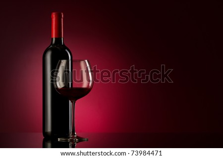 bottle with red wine and glass on a red gradient - stock photo