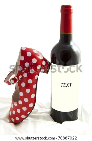 Bottle with red wine and spanish dotted red white shoe isolated on satin