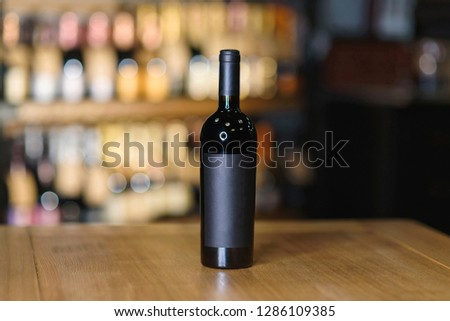 bottle with red wine on wooden table at cellar
